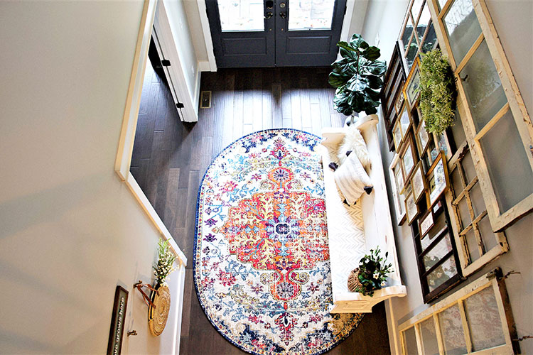 An aerial view of a vintage styled entryway and a colorful rug.