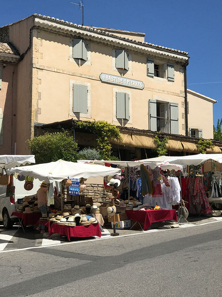 A flea market spotlighting white awnings and red tables covered in antiques.