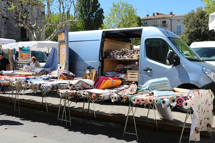 A truck at a Provence market loaded with multi-colored rugs.