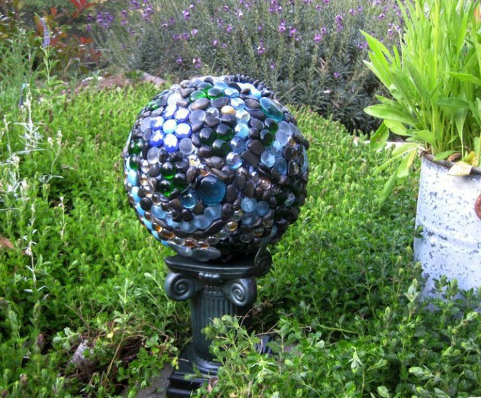 "The bowling ball, now ""garden art"" on a stand in the garden. Later it fell off this plastic stand, so another place had to be found."