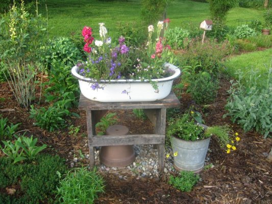 A simple old enamel pan on a wooden stand is centered in the garden bed
