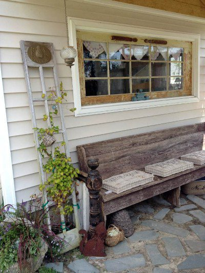 Kim Trudo's porch with a chippy white trellis and an old window made from a door!