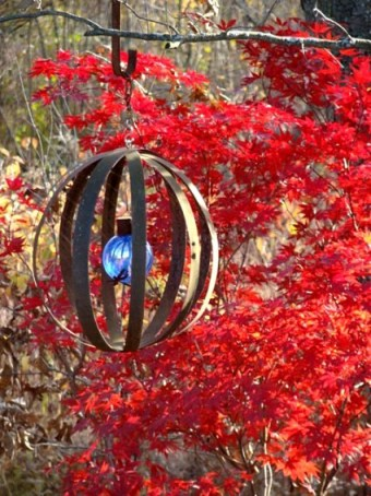 Lark Kulikowski says, I love to recycle and create art. This sphere is made from barrel strappings and a blue glass ball. The Japanese Maple is a bonus.