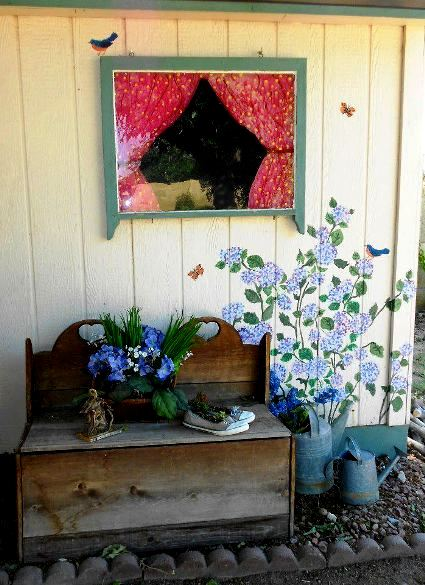 Keri Little painted flowers and a window on the side of her garden shed, complete with lace curtains!
