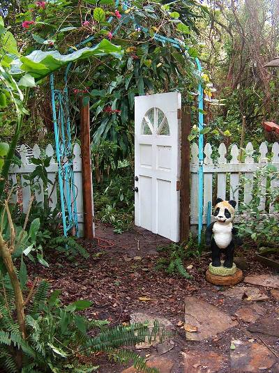 An old white front door accents the arbor