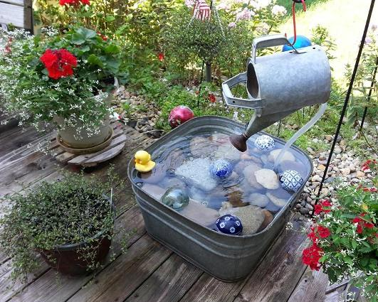 Nancy Carter hung a watering can to pour into her tub pond