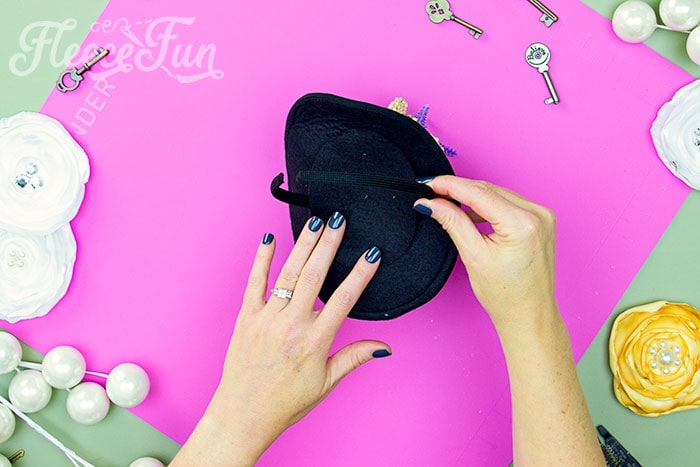 Adding a headband to the mini top hat. Learn how to make a mini top hat with this free pattern and tutorial. I love that there is a sew and no sew option. The free template makes this costume idea easy to make at home.
