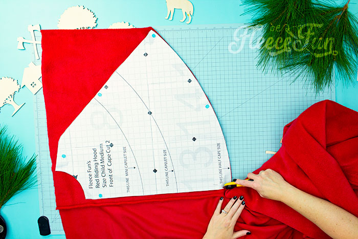 two front pieces cut out on fabric.Will keep the chill from nipping, but not the wolves. This cape has a video tutorial with a FREE sewing pattern. It's only six steps - looks DIY easy! Love this fleece sewing Project - Red Riding Hood Cape Pattern. It's a great costume pattern that has a classic look. It can work for different costumes. Perfect for Halloween. I love how the sewing tutorial is geared for beginners. It's a great beginner sewing project.