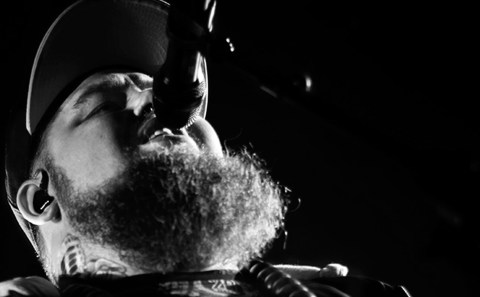 Rag 'n' Bone Man in black and white sings into mic