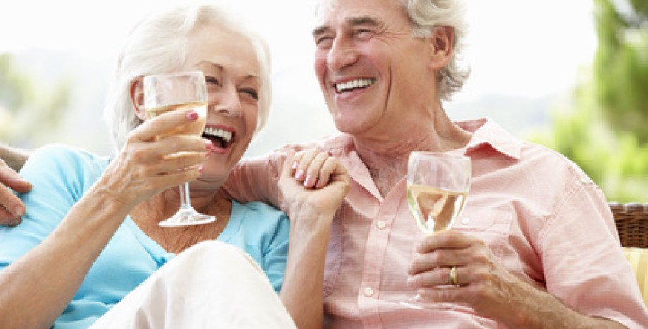 Senior Couple Sitting On Outdoor Seat Together Drinking Wine