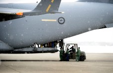 Members of the Japanese Self Defence Force brave a snowstorm to load a RAAF C-17A with disaster relief supplies