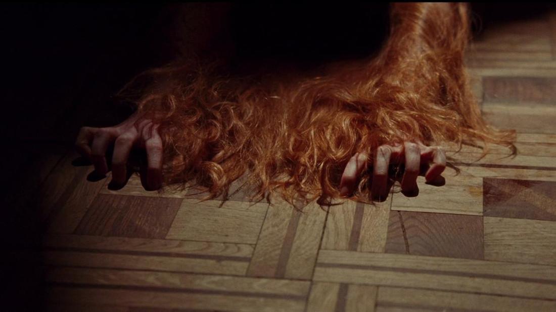 Susie Bannion (Dakota Johnson) clawing the floor in the Suspiria remake