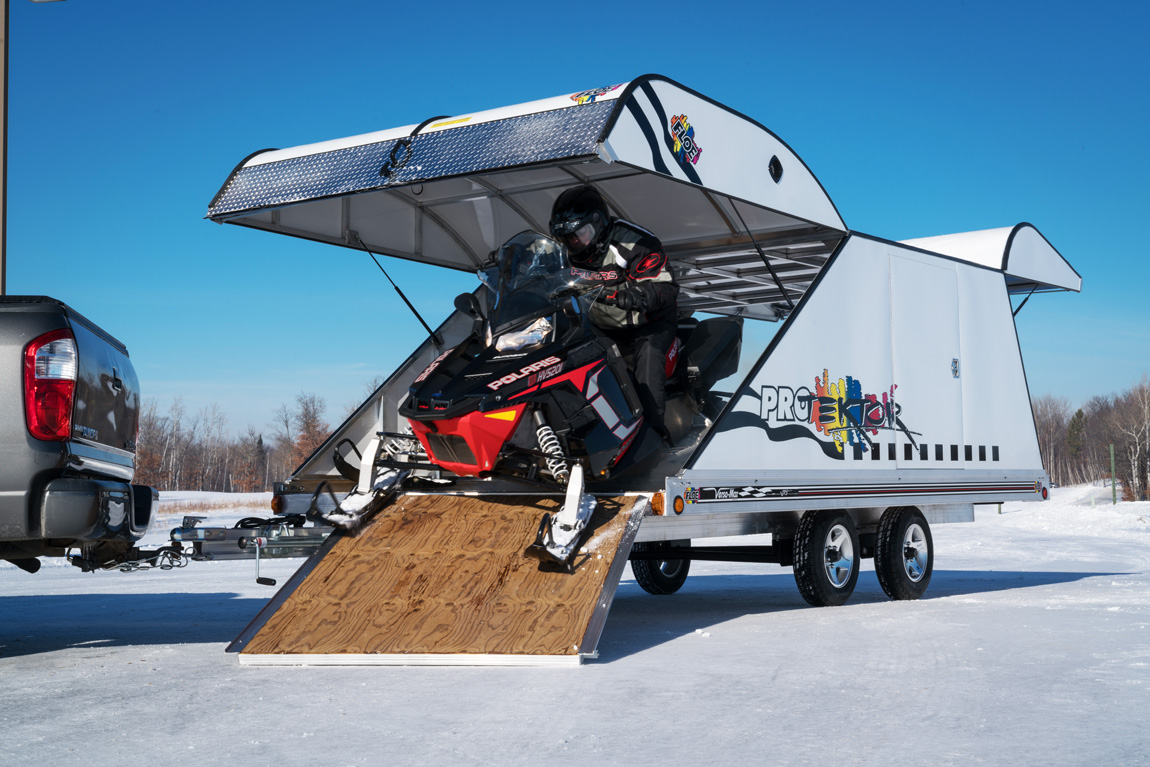 Snowmobile being unloaded from the Pro-Tecktor trailer.