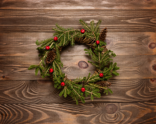 Pine and berry wreath on wooden background