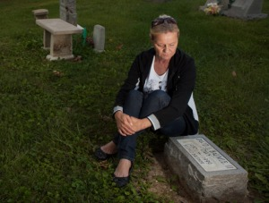 Udosha Baumle sits by the gravestone of her son Davy, who died at age 12 of liver failure after taking Maximum Strength Tylenol Sore Throat. Photo: Melanie Burford for ProPublica