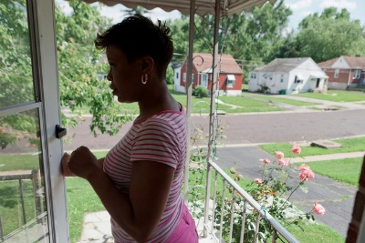 """Rosalyn Turner stands on the doorstep of her home in Jennings. Turner was sued over an unpaid sewer bill that was her landlord's responsibility and an unpaid car loan she took out ten years prior. """"It's hard not to go crazy and stress out, you know,"""" she said. Photo: Dan Gill for ProPublica"""