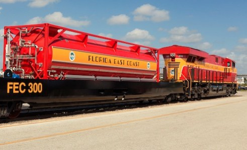 Red and gold FEC locomotive with an LNG tender car, a potential 'bomb train.'