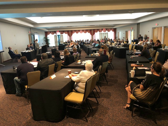 A large room filled with tables at which municipal leaders are listening to Broward Commissioner Beam Furr and Weston Mayor Dan Stermer