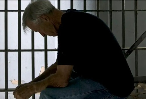 Gray haired man sitting on bunk in prison cell