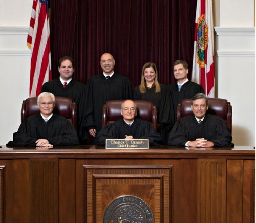 Seven justices in black robes, six men and one woman
