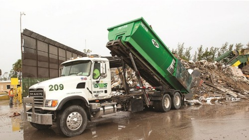 A green and white Southern Waste Systems truck dumping trash
