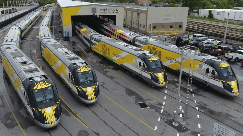 Six yellow and black Brightline trains together at the workshop in West Palm Beach