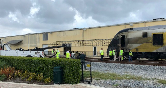 Workers in yellow vests stand beside the blackened engine of a Brightline train. Other workers are using a tow truck to haul away a wrecked Maserati.