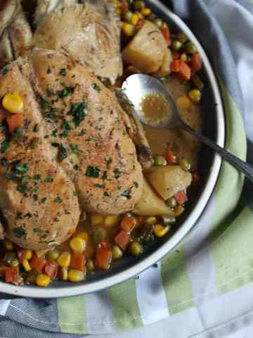 a Platter with Lemon Chicken Roast in it and a spoon resting in some broth
