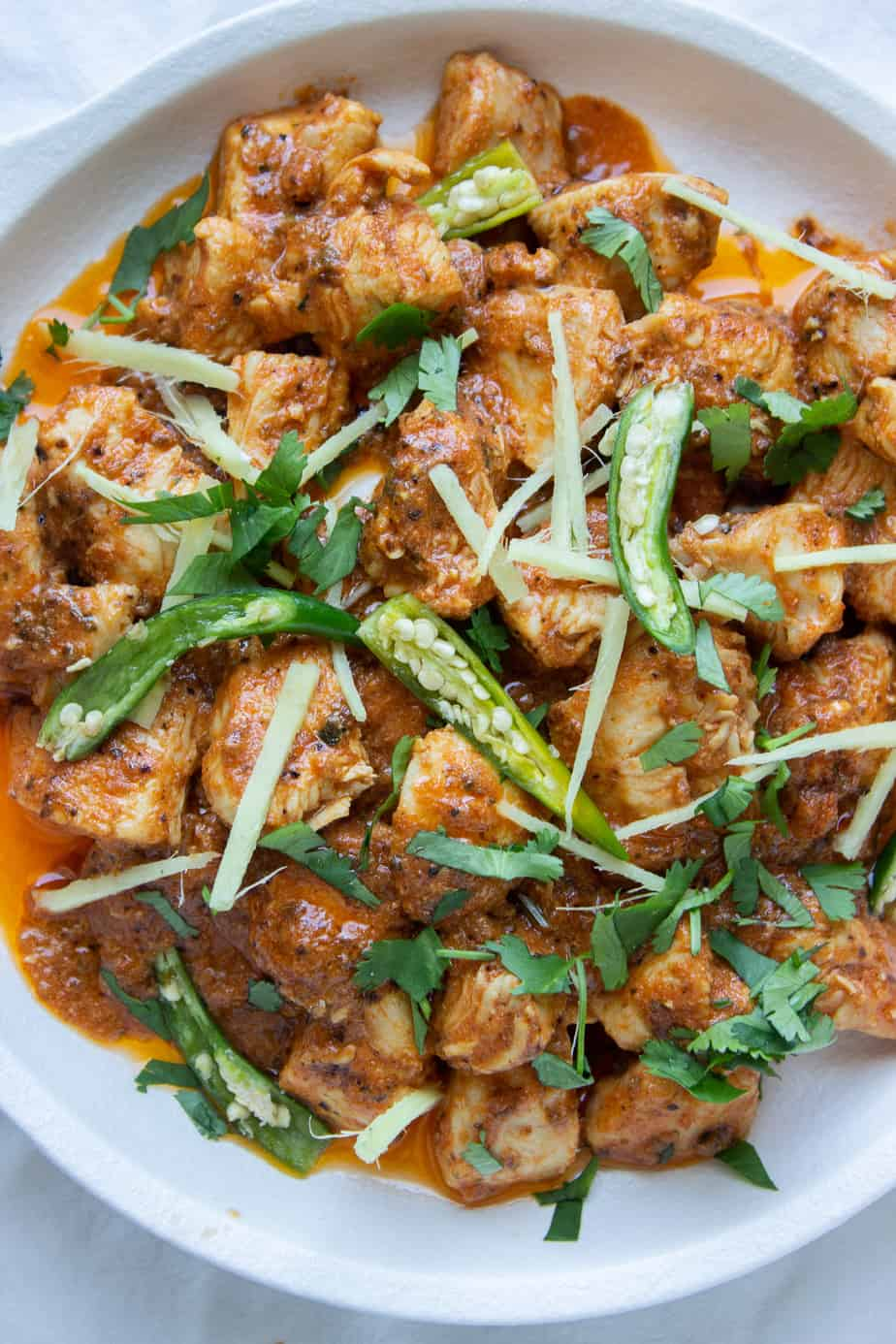 a close up of a dish of Karhai Chicken with green chilies,ciilantro and ginge