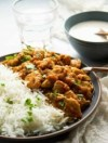 a three quarter angle view of a plate of chicken masala, a bowl of raita and a glass of water
