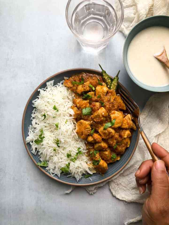 A plate with rice and chicken masala, a hand holding a fork. a bowl of spiced yoghurt and a glass of water.