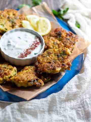 3/4 view of a plate of cauliflower fritters with the mint yogurt in the center