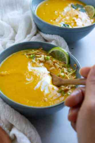 a hand placing a spoon in a bowl of soup as if to take a bite. pictured: instant pot carrot soup in a blue bowl