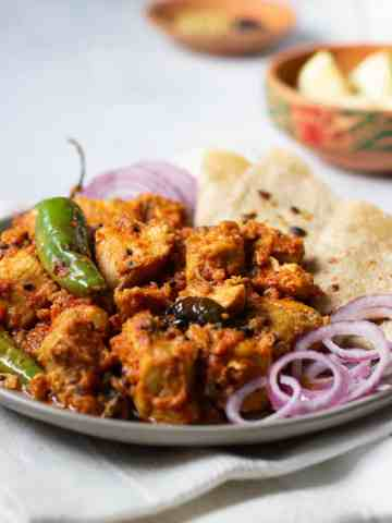 A plate of Achar Chicken with some onions and roti