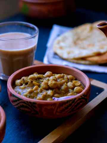 Puri Chole in a dish, chai in a glass behind it, pooris on a newspaper