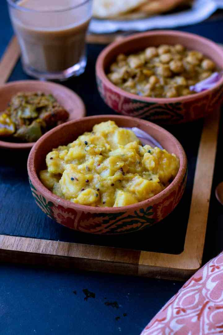 Poori Aloo in a small dish, achar, cholay and chai