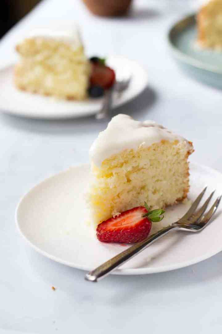 A slice of Easy Lemon Cake with Cream Cheese Glaze and a half strawberry