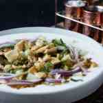 dish of chaat, copper containers in the background