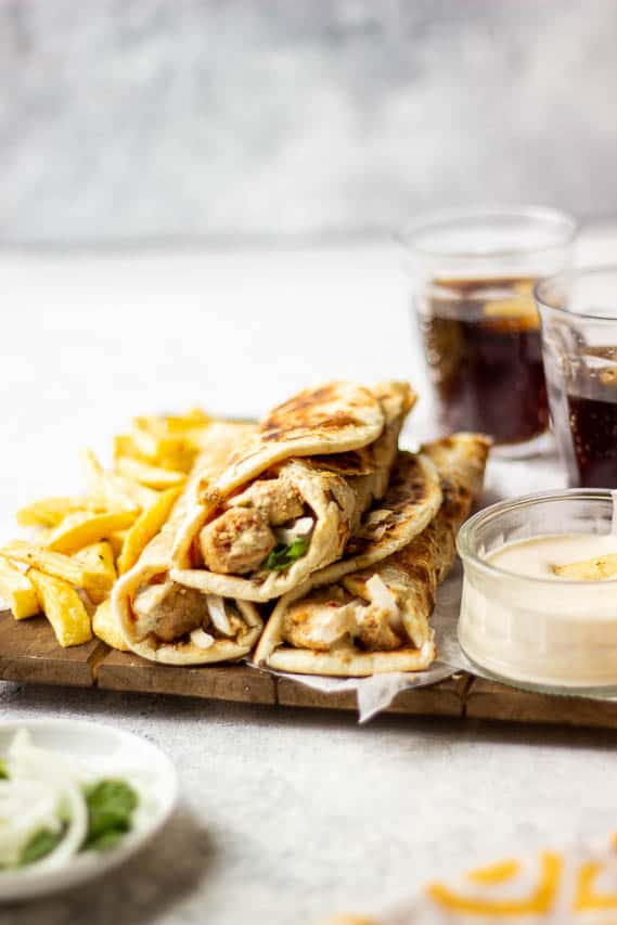 3 boti rolls stacked together, garlic mayo on the side, fries in the frame along with glasses of coke in the background
