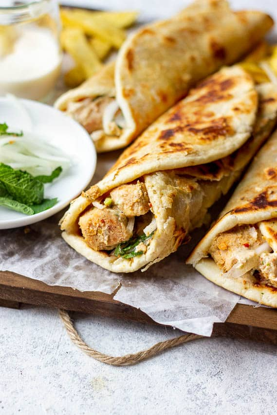Partial view of chicken paratha roll on a wooden tray. partial of mint and onions.