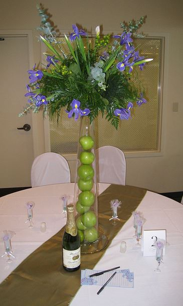 Tall wedding centerpiece with purple flowers and green