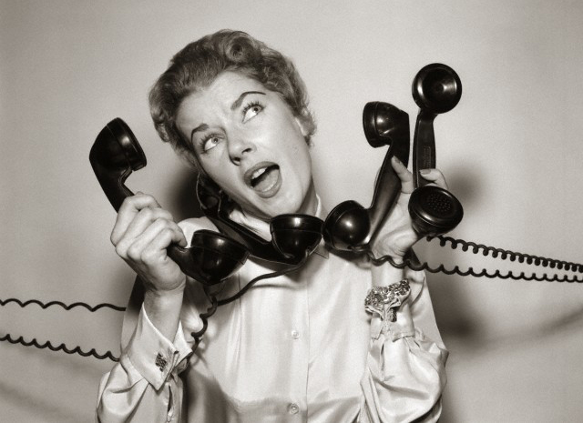 1950 --- 1950s 1960s Overwhelmed Stressed Woman Answering Four Black Telephone Phone Receivers At One Time --- Image by © DeBrocke/ClassicStock/Corbis