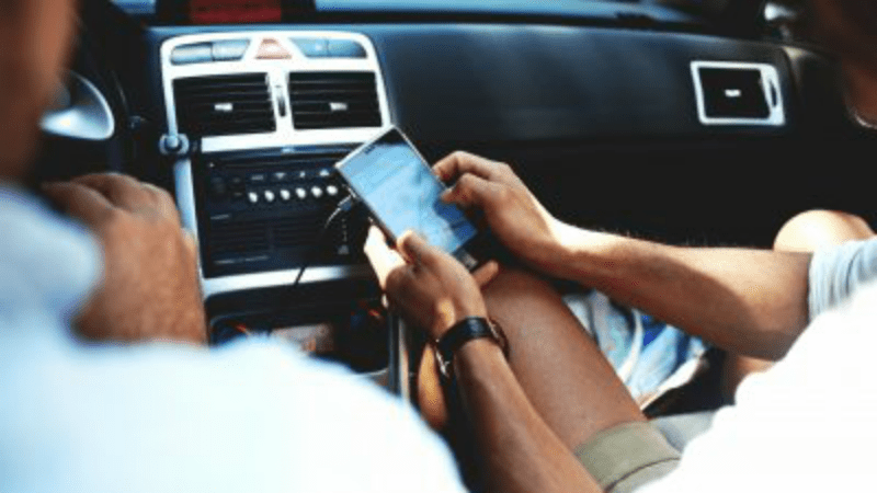 Couple in car using smartphone app for directions on locums assignment