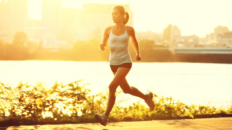 Healthy woman running outdoors at sunset