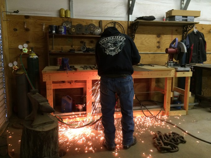 Michael hand cuts steel sheet with the torch for a recent project: The Bottom of the Stairs (photos coming soon).