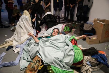 Four people covered in numerous blankets and clothing are rolling on the floor. A group of people stand by to take pictures of the scene.