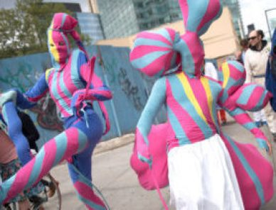 Two people wearing morph suits that are bright pink and teal stripes are dancing in a parade as onlookers are nearby. One performer wears a white pant over their suit as another one adds a periwinkle blue to their suit.