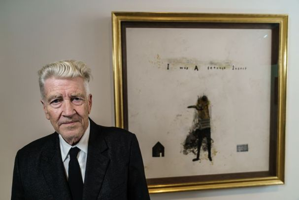 a man named David Lynch standing in front of a painting