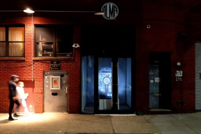 A photo taken outside the Flux Factory gallery at night, where a light exhibit is taking place inside. Two people are walking underneath a street lamp by the gallery.