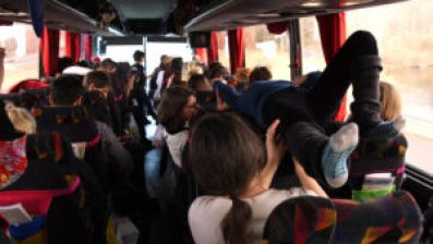 A photo taken from the back of children on a bus, one is lying flat on their back over the seats.